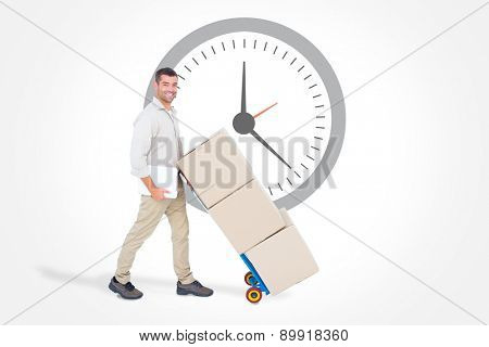 Happy delivery man pushing trolley of boxes against clock
