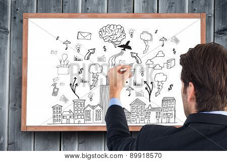 Rear view of businessman writing with a white chalk against blackboard with copy space on wooden board
