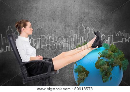 Businesswoman sitting on swivel chair with feet up against hand drawn city plan