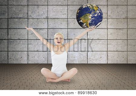 Toned young woman sitting with arms outstretched against grey room