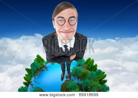 Geeky businessman smiling at camera against bright blue sky over clouds
