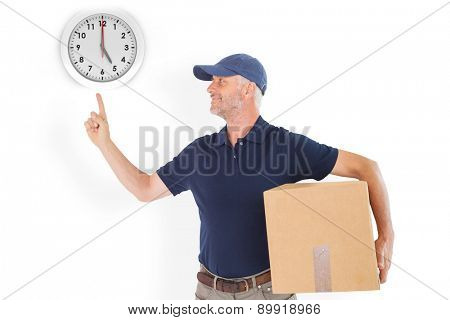 Happy delivery man holding cardboard box and pointing up against five o clock