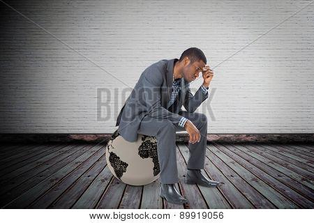 Thinking businessman sitting against grey room