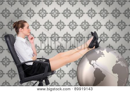 Businesswoman sitting on swivel chair with feet up against grey wallpaper