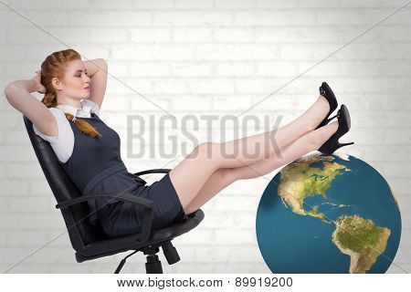 Businesswoman sitting on swivel chair against white wall