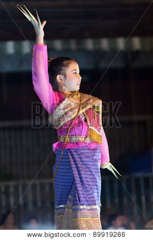 CHIANG MAI, THAILAND, JANUARY 04, 2015: A woman is performing a Thai traditional dance at an outdoor stage during the Saturday night street market in Chiang Mai, Thailand
