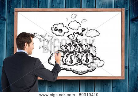 Businessman standing back to camera writing with marker against blackboard with copy space on wooden board