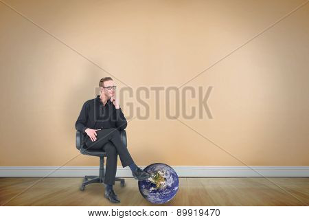 Thoughtful businessman sitting on a swivel chair against room with wooden floor