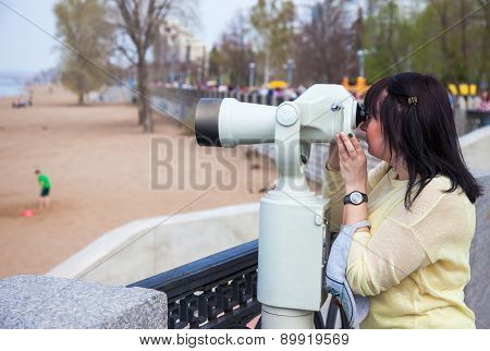 Young Woman Looking Through The Coin Operated Binocular