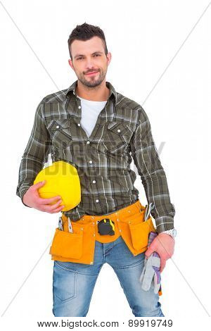 Handyman wearing tool belt while holding helmet and gloves on white background