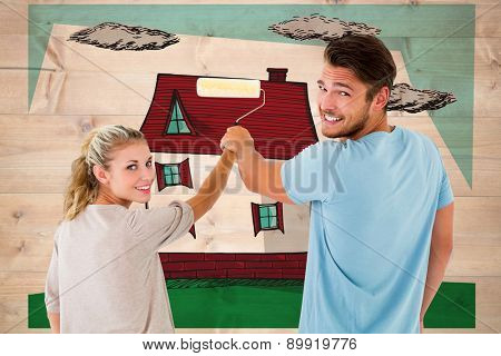 Young couple painting with roller against bleached wooden planks background