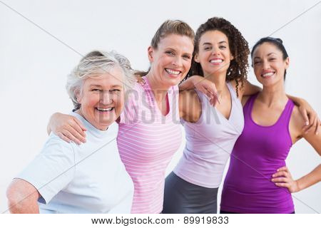 Portrait of happy friends standing arms around in fitness studio