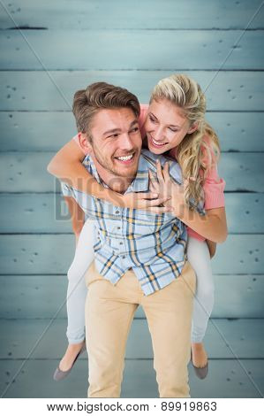 Handsome man giving piggy back to his girlfriend against wooden planks