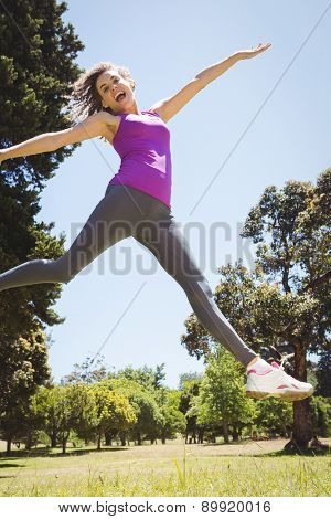 Fit woman leaping in the park on a sunny day