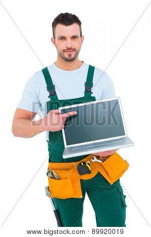 Smiling construction worker holding laptop on white backboard