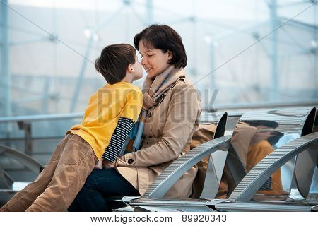Loving mother and son hugging at airport