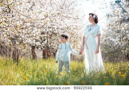 Happy young woman and her child in blooming garden