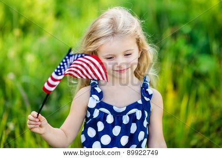 Pretty Pensive Little Girl With Long Curly Blond Hair Holding An American Flag And Smiling On Sunny