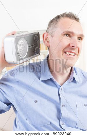 Hearing impaired man trying to listen radio at home