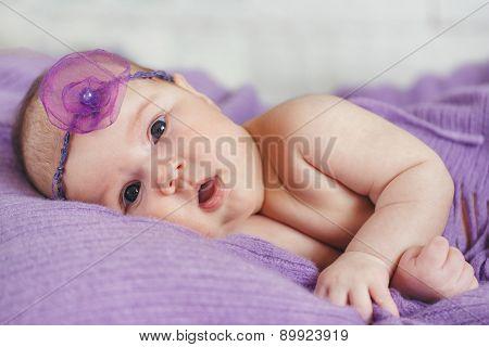 Awake newborn baby in her bed