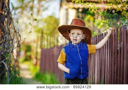 Portrait Of A Little Boy Standing In A Big Hat In The Wooden Fence
