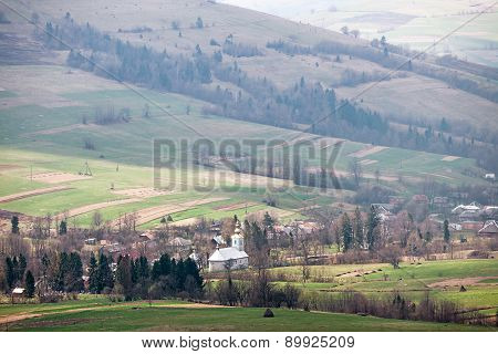Typical Mountain Village With A Church In Carpathians