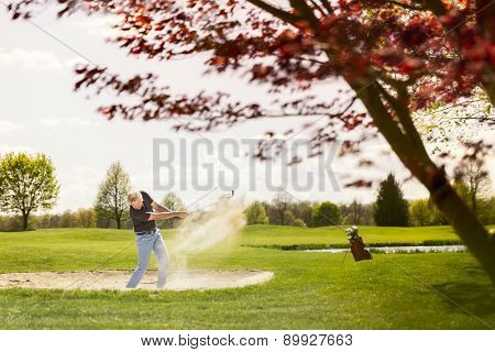 Senior golf player hitting ball from sand bunker, with golf bag in background.