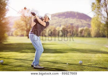 Senior golf player teeing off with golf club at sunset.