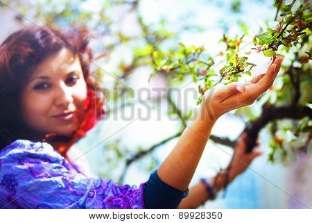Young Poetic Woman With Magnolia Tree In The Spring Time. Woman Holding Flower.