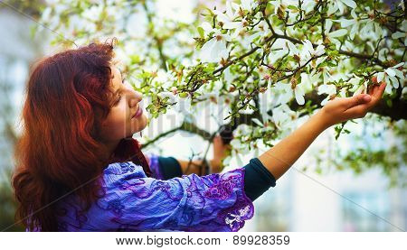 Young Poetic Woman With Magnolia Tree In The Spring Time. Woman Holding Flower