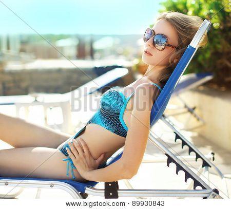 Portrait Of Beautiful Woman In Swimsuit Sunbathing On The Beach