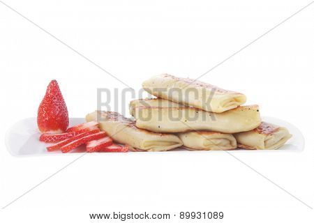 russian food - heap of sweet pancake filled with cottage cheese with strawberry served on white plate isolated over white