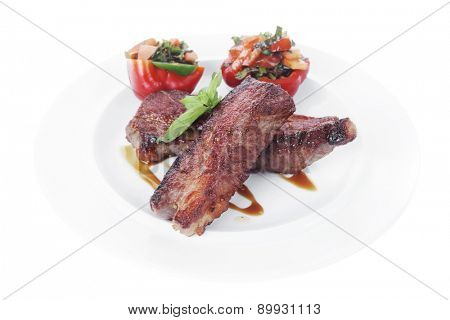 fresh red beef meat steak barbecue garnished vegetable salad and basil  in half of pepper bell on white plate isolated over white background