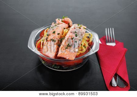 fresh fried natural pink salmon on italian traditional tagliatelle backed with tomato and vegetables served over black wooden table