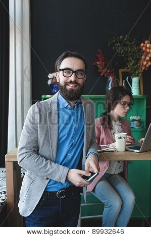Businessman In Glasses With Smartphone Over Woman Working On Background