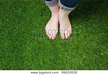 Woman legs in jeans standing  on grass