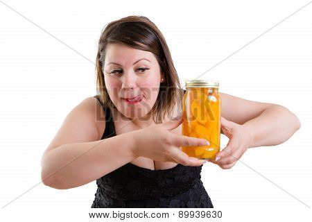 Woman Licking Her Lips And Eyeing A Jar Of Peaches