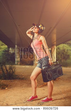 Beautiful hip hop woman with a tape recorder and headphones enjoying the music