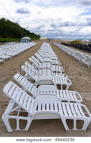 Row Of White Chairs For Sunbathing On The Sandy Beach