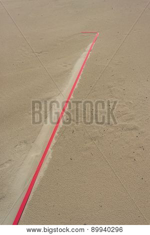 Detail Of A Red Line In The Sand After Rain