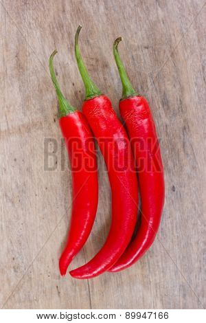 Hot red chili or chilli peppers over wooden background