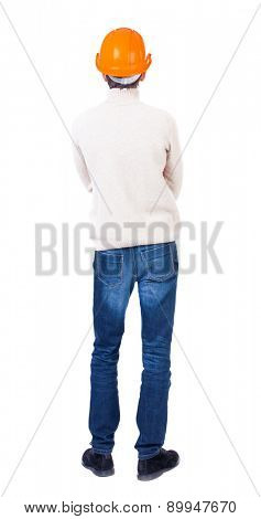 Backview of engineer in construction helmet stands. Standing young guy. Rear view people collection. Isolated over white. Construction worker with his arms crossed looks at the process of work
