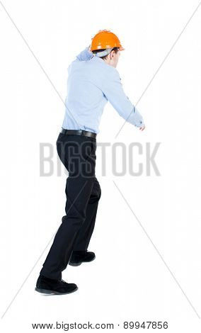 Back view of running engineer in helmet. Walking guy in motion. Rear view people collection. Backside view of person. Isolated over white background. on top of a man holding a helmet runs