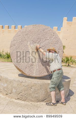 Taurodant, Morocco - tourists pose with old quern in front of historic ramparts
