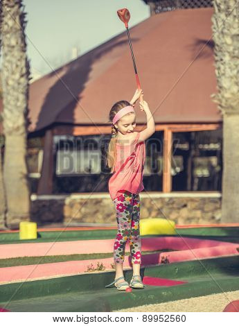 Cute smiling little girl playing golf