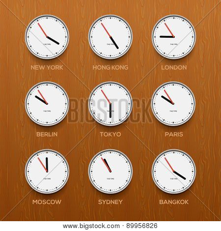 Timezone clocks showing different time, wooden wall background