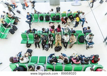 Passengers Wait On Benches For The Departure Of Their Flight