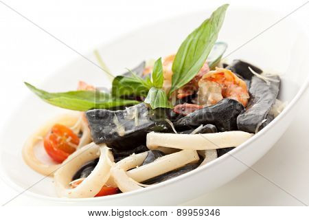 Black Pasta with Seafood and Parmesan Cheese. Garnished with Basil Leaf