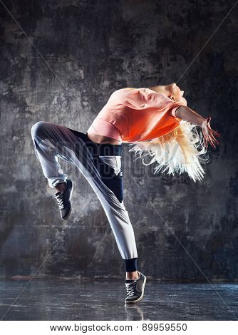 Young woman modern dancer. On stone wall background.