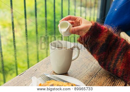 Woman Pouring Milk In Her Tea